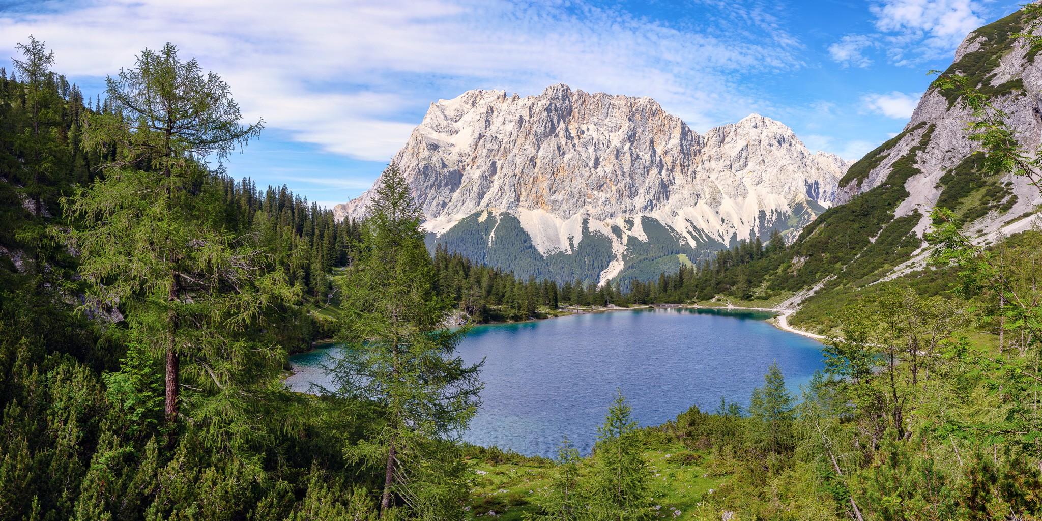 Blick auf den idyllischen Seebensee aus dem Bergwald mit Lärchen und Latschen. Im Hintergrund das Zugspitzmassiv mit dem Schneefernerkopf.