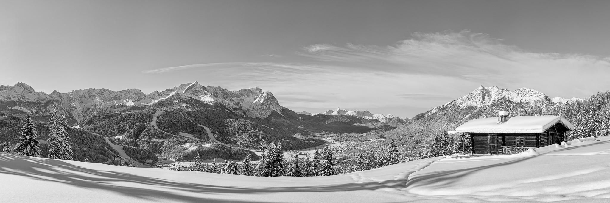 Schwarz Weiß - Traumwetter in Garmisch-Partenkirchen. Blick auf das verschneite Garmisch-Partenkirchen und das Bergpanorama mit Zugspitze.