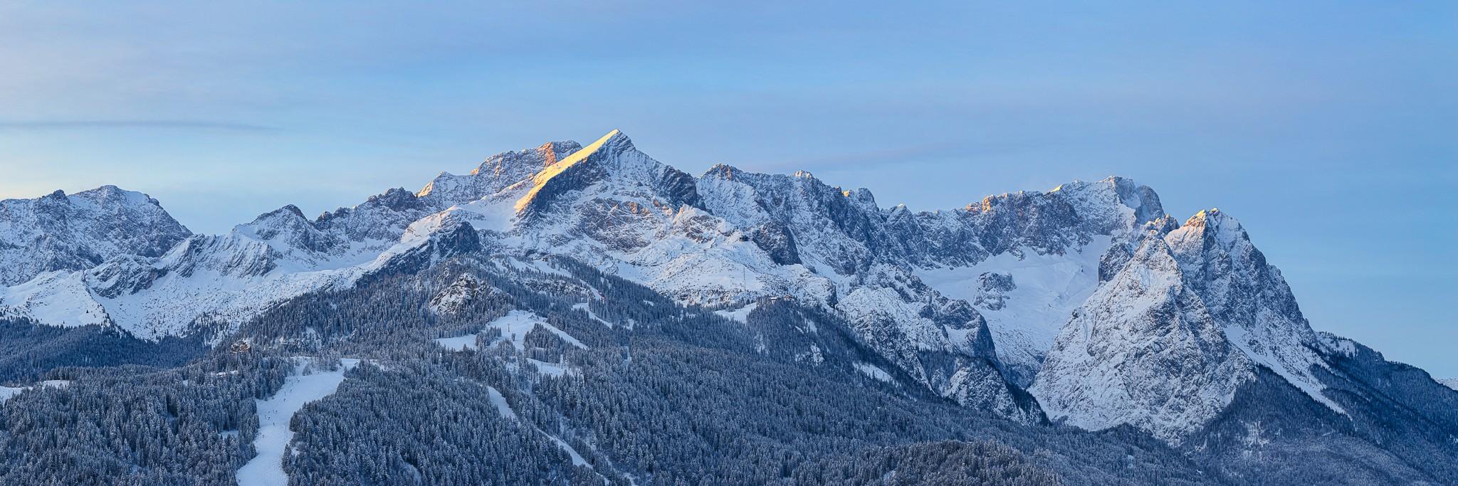 Das erste Sonnenlicht streift die Bergspitzen über Garmisch-Partenkirchen. Alpspitze, Zugspitze und Waxenstein mit Pulverschnee!