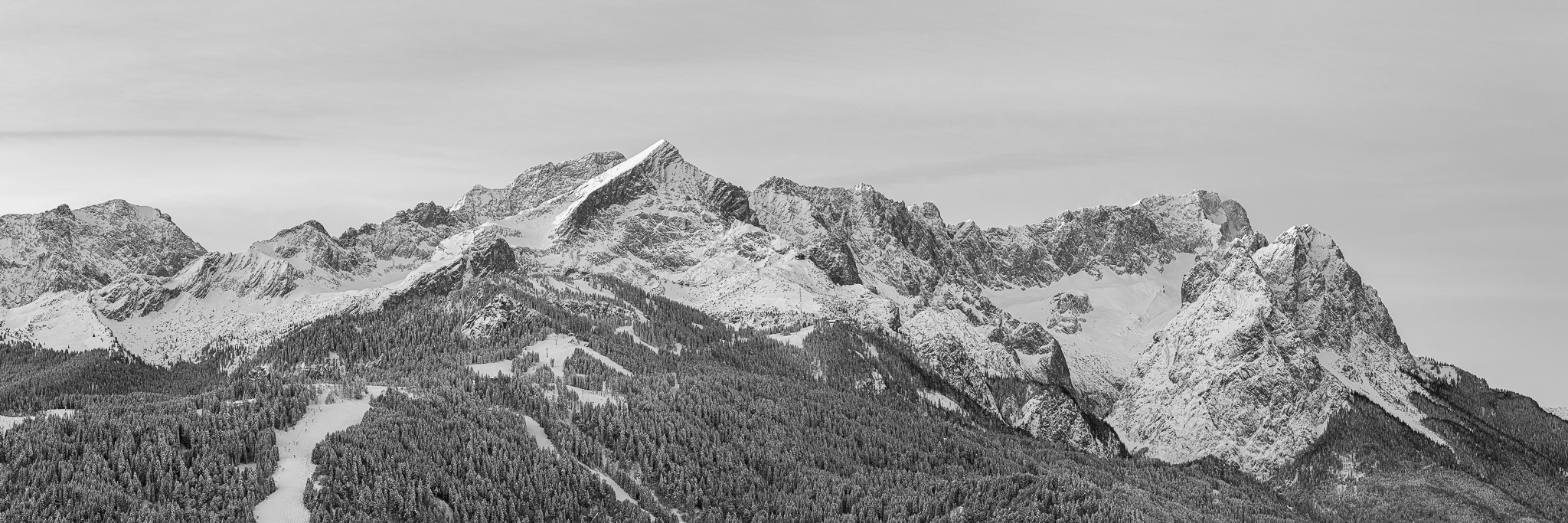 Schwarz-Weiß: Das erste Sonnenlicht streift die Bergspitzen über Garmisch-Partenkirchen. Alpspitze, Zugspitze und Waxenstein