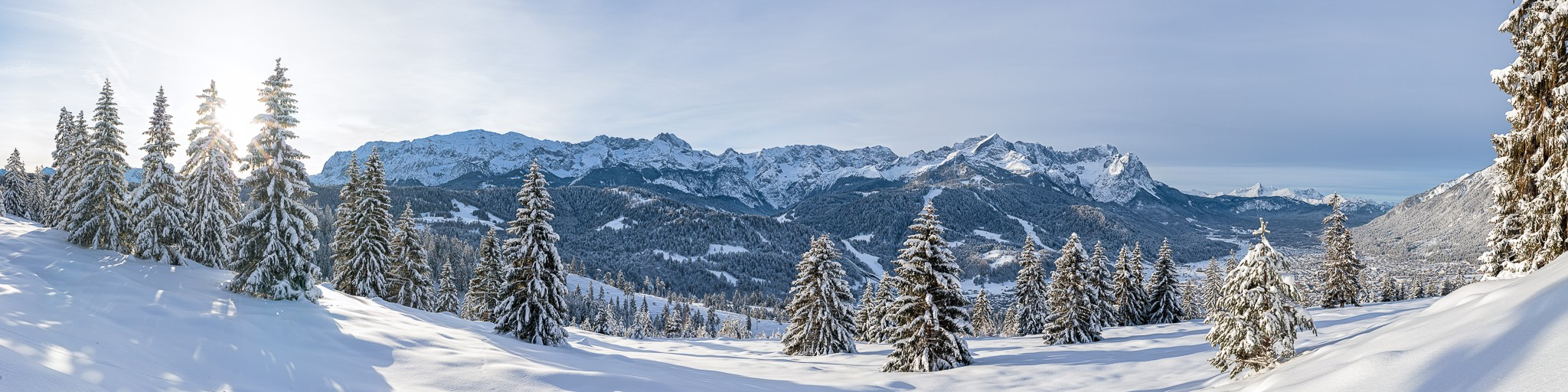 Winterwald oberhalb von Garmisch-Partenkirchen mit einem wunderbaren Panoramablick auf das Wettersteingebirge mit Zugspitze und Alpspitze.