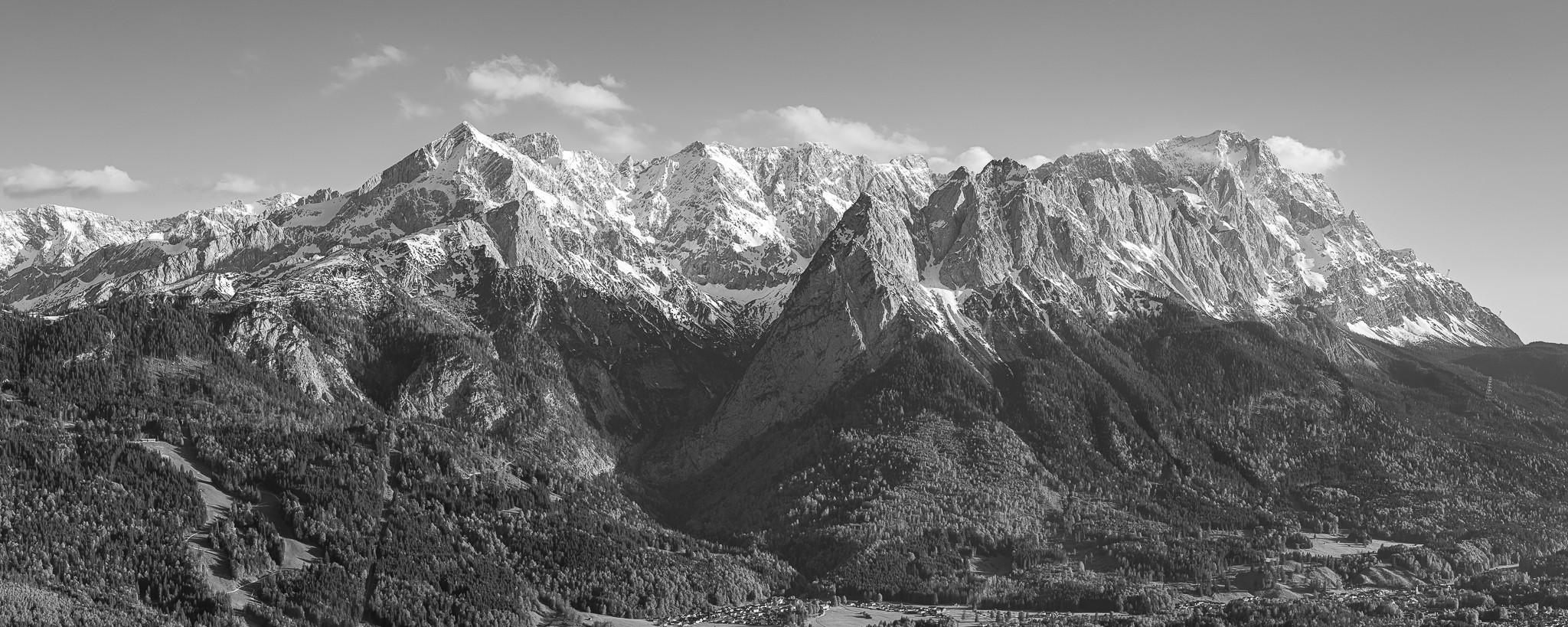 Die Alpspitze imponiert das Garmisch-Partenkirchener Bergpanorama. Mittig das Höllental und rechts die Zugspitze. Schwarz Weiß
