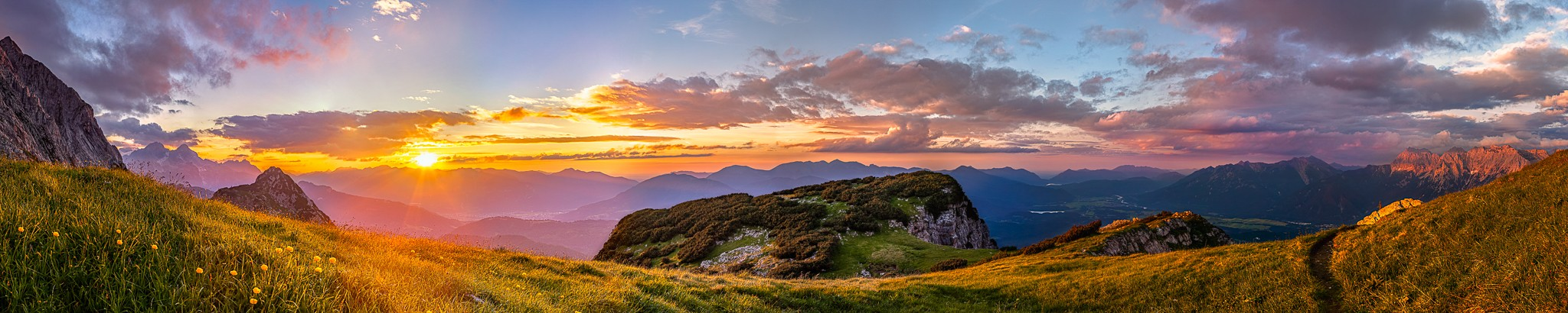Bei Sonnenuntergang am Gamsanger unterhalb der oberen Wettersteinspitze angekommen werden die Wolken über dem Werdenfelser Land vom Abendrot erleuchtet. Blick auf Garmisch -Partenkirchen mit Berglandschaft.