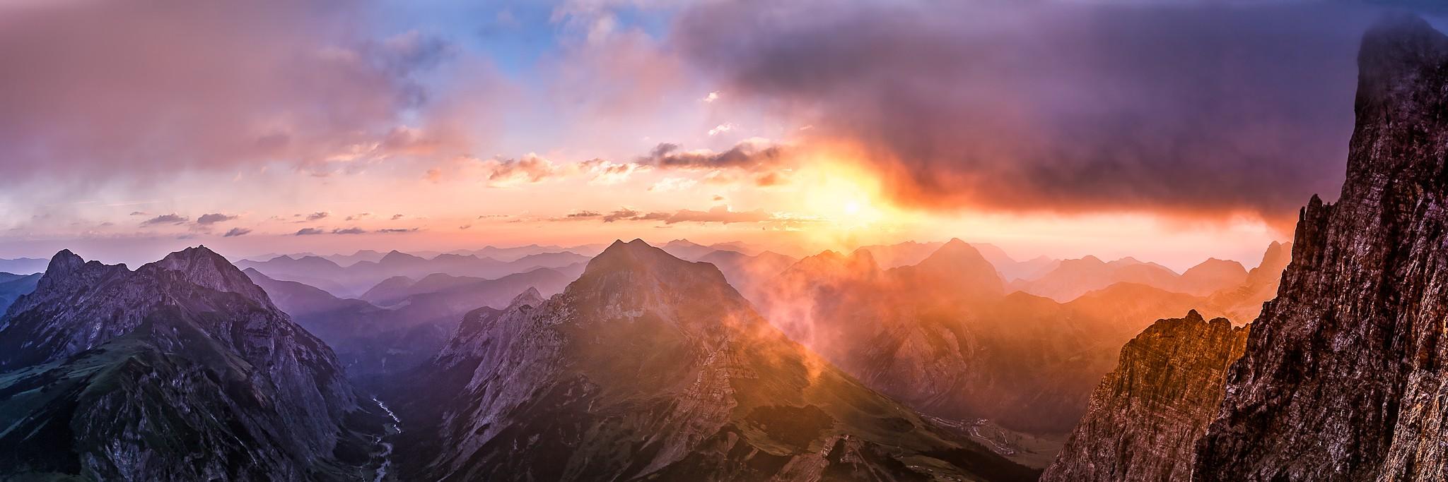 Zunächst war es ein ganz normaler Sonnenaufgang an der Laliderer Wand, doch dann zog von rechts eine düstere Wolke über die Dreizinkenspitze. Berglandschaft in den Alpen - Karwendelhauptkamm.