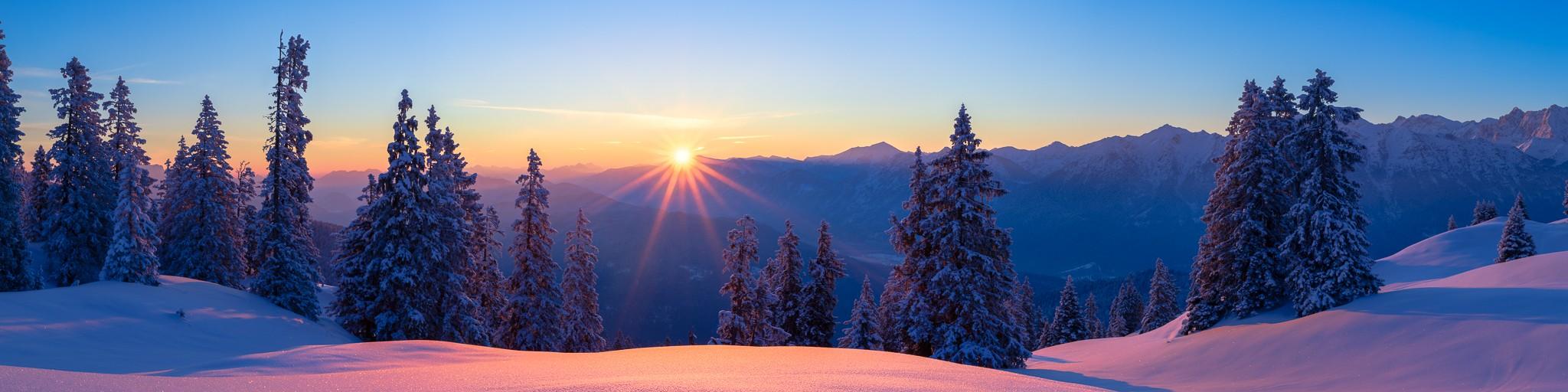 Der Pulverschnee funkelt mit der aufgehenden Sonne - Schnee auf den Bäumen und im Tal