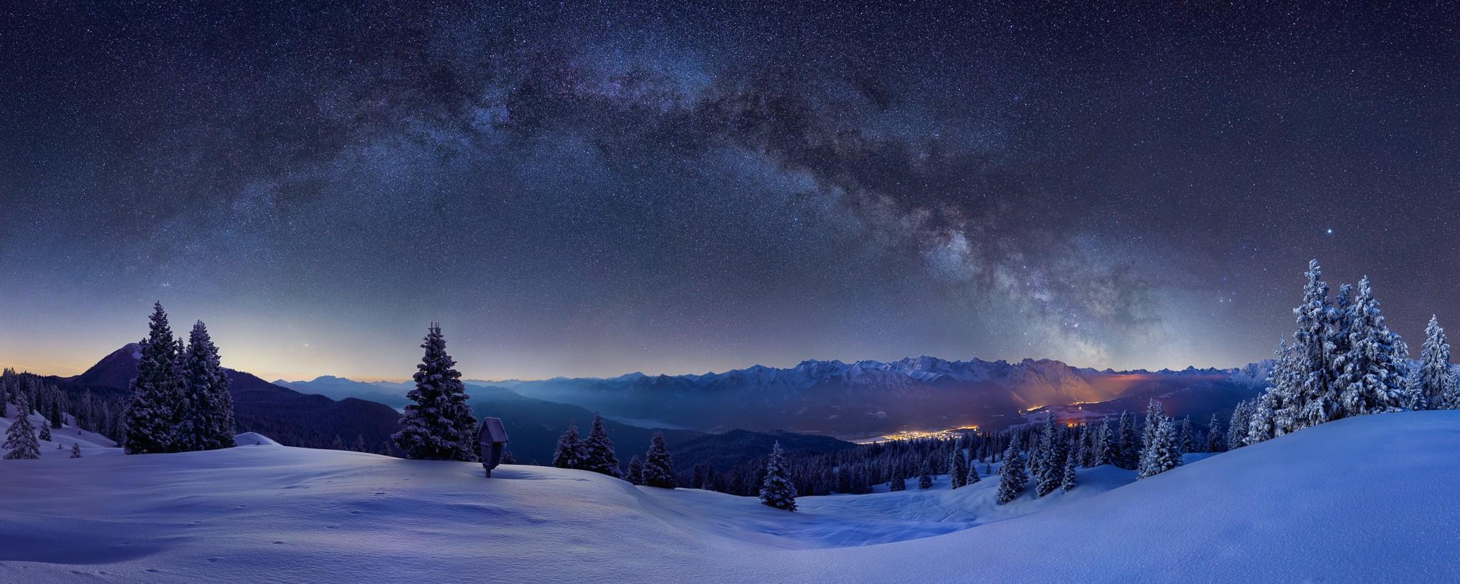 Im Bild ist die Milchstraße mit ihrem galaktischen Zentrum auf der rechten Seite zu sehen. Im Vordergrund ist die Wallgauer Alm. Panorama