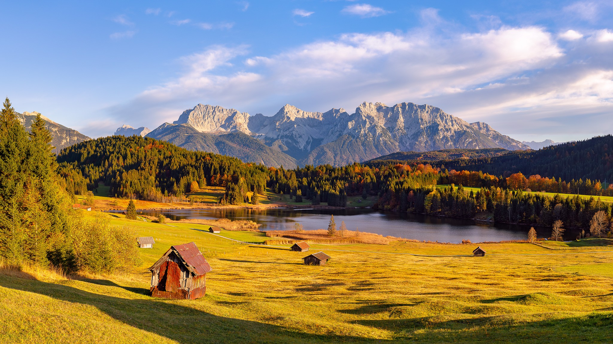 Die Landschaft rund um den Wagenbrüchsee (Geroldsee) ist zu jeder Jahreszeit ein Genuss. Im Vordergrund auf den Buckelwiesen stehen die schiefe Wiesmahdhütte und einige Heustadel.